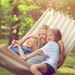 mother + daughters smiling in hammock
