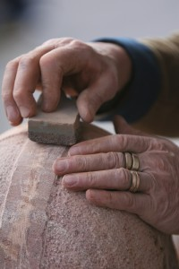 hands carving wood